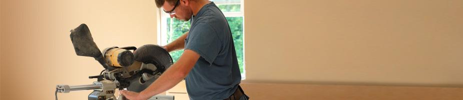 finish carpenter cutting trim with a miter saw