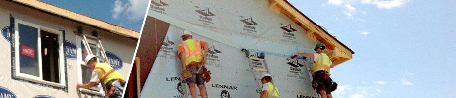 carpentry crew installing housewrap, windows and doors